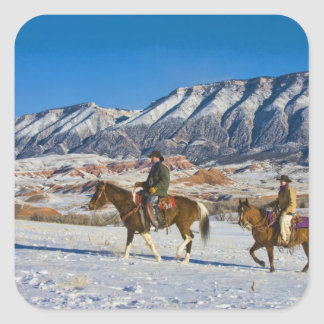 Cowboy and Cowgirl riding Horse through the Snow Square Sticker