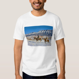 Cowboy and Cowgirl riding Horse through the Snow Tshirts