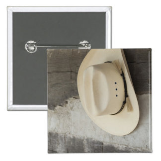 Cowboy hat hanging on wall of log cabin buttons