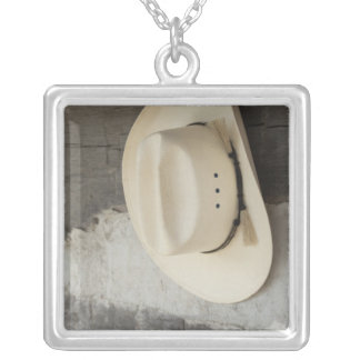 Cowboy hat hanging on wall of log cabin necklace