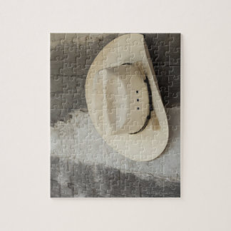 Cowboy hat hanging on wall of log cabin puzzles