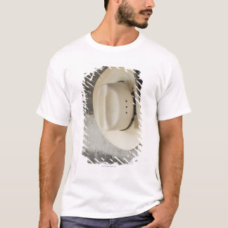 Cowboy hat hanging on wall of log cabin T-Shirt