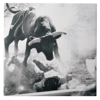 Cowboy on ground after falling off bull ceramic tile