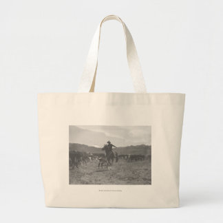 Cowboy roping a calf for spring branding. large tote bag