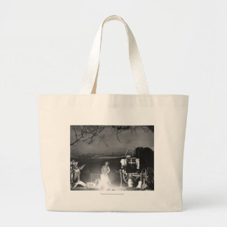 Cowboys playing and singing around a campfire large tote bag