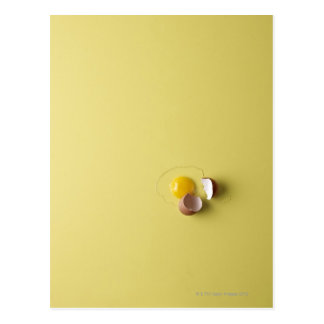 cracked egg on yellow background postcard