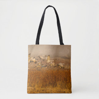 Cranes over a golden field tote bag
