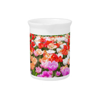 Crystal ball with various colored tulips on white beverage pitcher