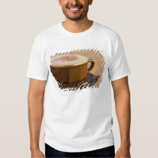 Cup of cappuccino with cocoa powder tee shirts
