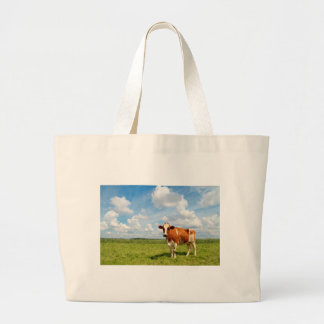 Curious cow standing on meadow bag
