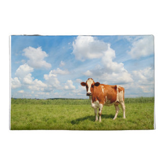Curious cow standing on meadow travel accessory bag