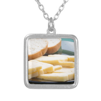 Cut slices of cheese on a plate close-up silver plated necklace