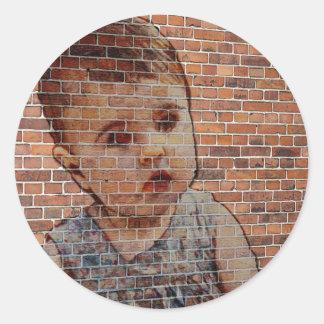 Cute baby on brick wall. round sticker