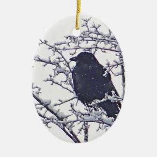 Cute black bird in snowy branches ceramic ornament