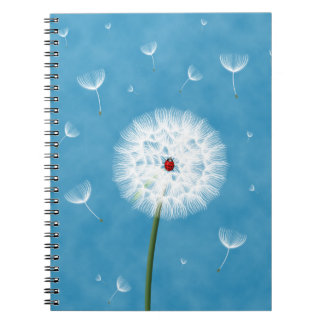 Cute ladybug sitting on top of a dandelion notebooks