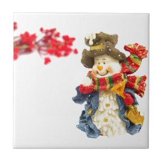 Cute snowman figurine with red berries on white ceramic tile