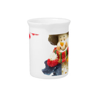 Cute snowman figurine with red berries on white pitcher