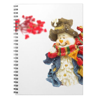 Cute snowman figurine with red berries on white spiral notebook