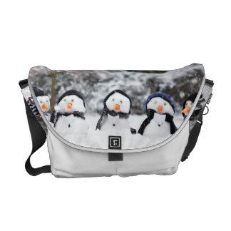 Cute snowmen dressed for winter messenger bag