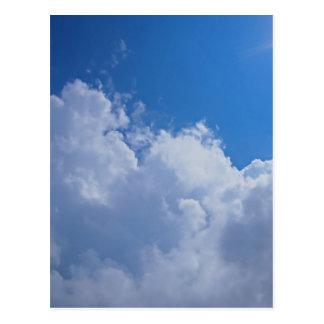 Dark clouds, blue sky and bright sun postcard
