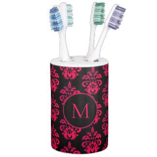 Dark pink monogram on black soap dispenser and toothbrush holder