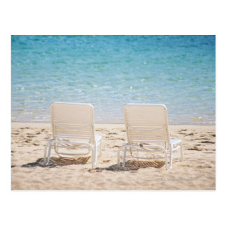 Deck chairs on sandy beach postcard