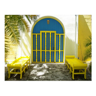 Decorated blue door with yellow benches postcard