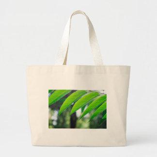 Defocused and blurred branch ailanthus large tote bag