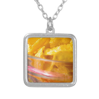 Defocused and blurred macro view of yellow flakes silver plated necklace