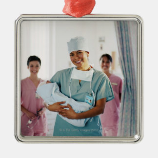 Delivery room nurse holding baby, nurses in metal ornament