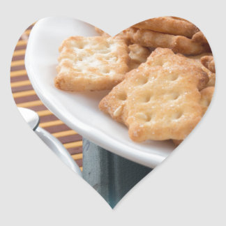 Detail of a cup of tea and a plate of crackers heart sticker