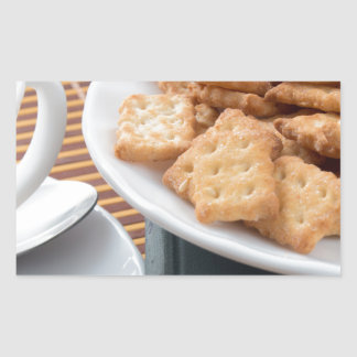 Detail of a cup of tea and a plate of crackers rectangular sticker