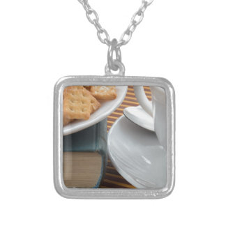 Detail of a cup of tea and a plate of crackers silver plated necklace