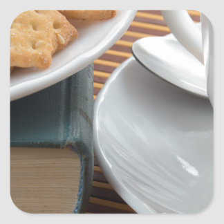 Detail of a cup of tea and a plate of crackers square sticker