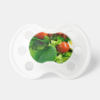 Detail of a plate with cherry tomatoes, herbs baby pacifier