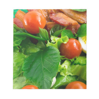 Detail of a plate with cherry tomatoes, herbs notepads