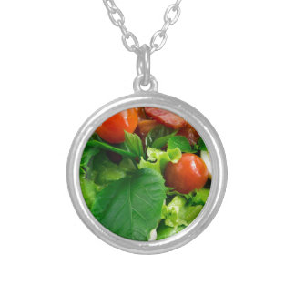 Detail of a plate with cherry tomatoes, herbs silver plated necklace