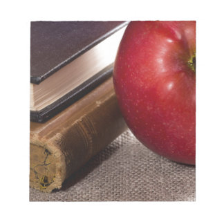 Detail of old books in hardcover and red apple notepad
