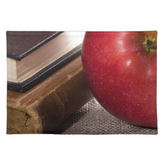 Detail of old books in hardcover and red apple placemat
