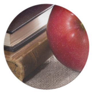 Detail of old books in hardcover and red apple plate