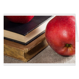 Detailed close-up view of the red apples and old card
