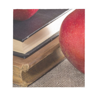Detailed close-up view of the red apples and old notepad