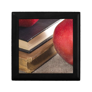 Detailed close-up view of the red apples and old small square gift box
