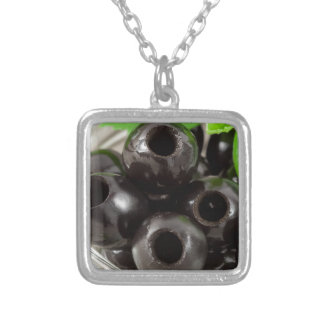 Detailed macro view of the black olives silver plated necklace