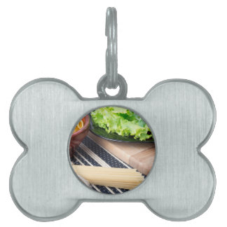 Diagonal composition on a table with a fresh salad pet ID tag