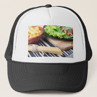 Diagonal composition on a table with a fresh salad trucker hat