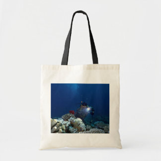 Diver shooting video on coral bed tote bags