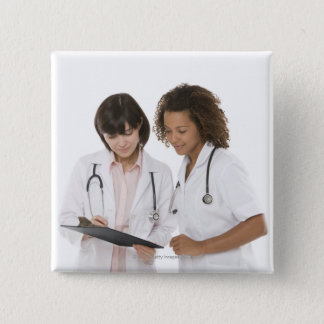 Doctors looking at clipboard 15 cm square badge