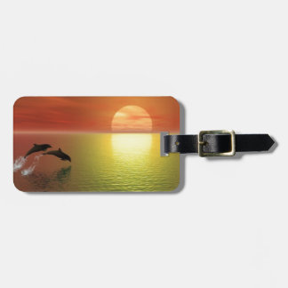 dolphins jumping ocean sunset luggage tag