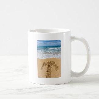 Drawing of palm tree on sandy beach coffee mug